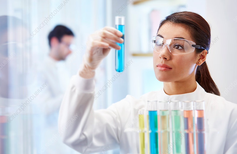 Woman looking at vial with blue fluid