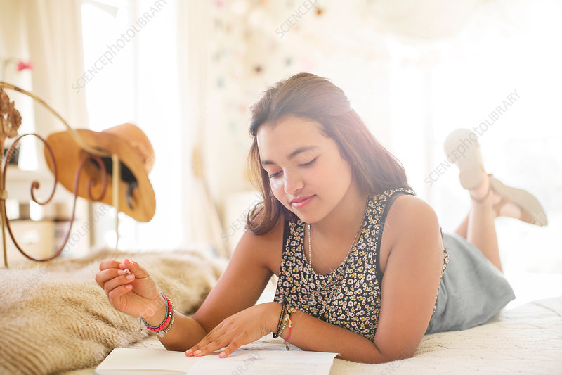 Girl lying on bed and writing in notebook