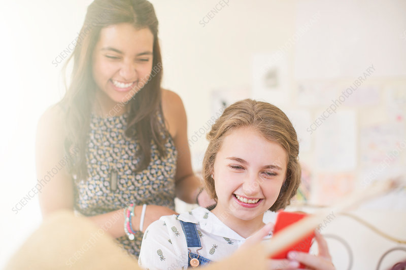 Girls sharing smartphone and smiling