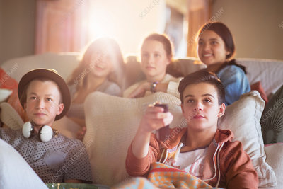 Group of teenagers watching tv on sofa
