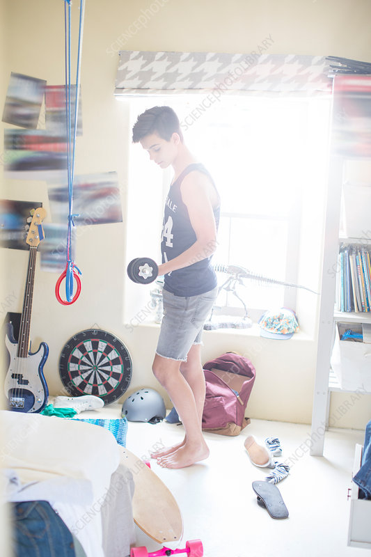 Boy exercising with dumb bell in his room