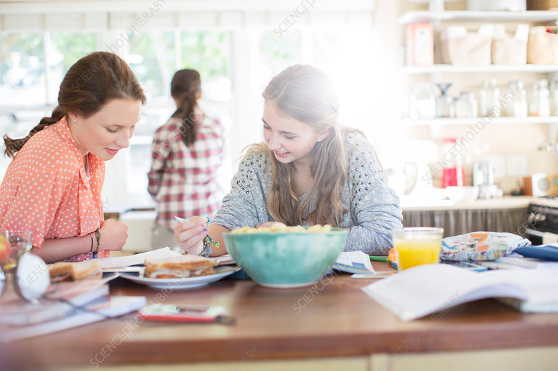 Girls learning at table in kitchen