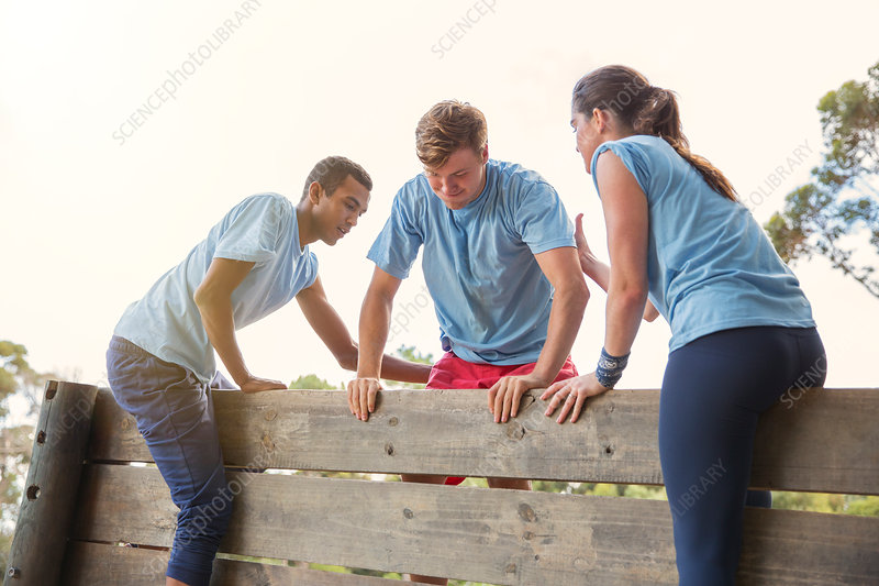 Teammates helping man over wall