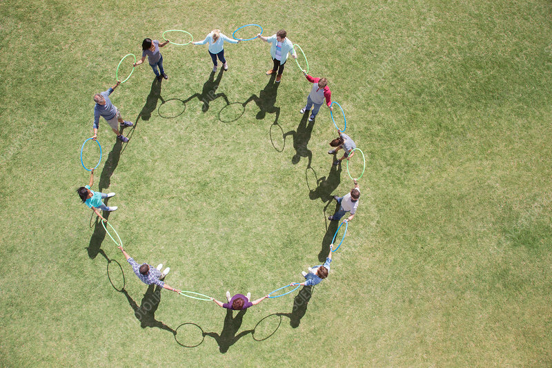 Team connected in circle in sunny field