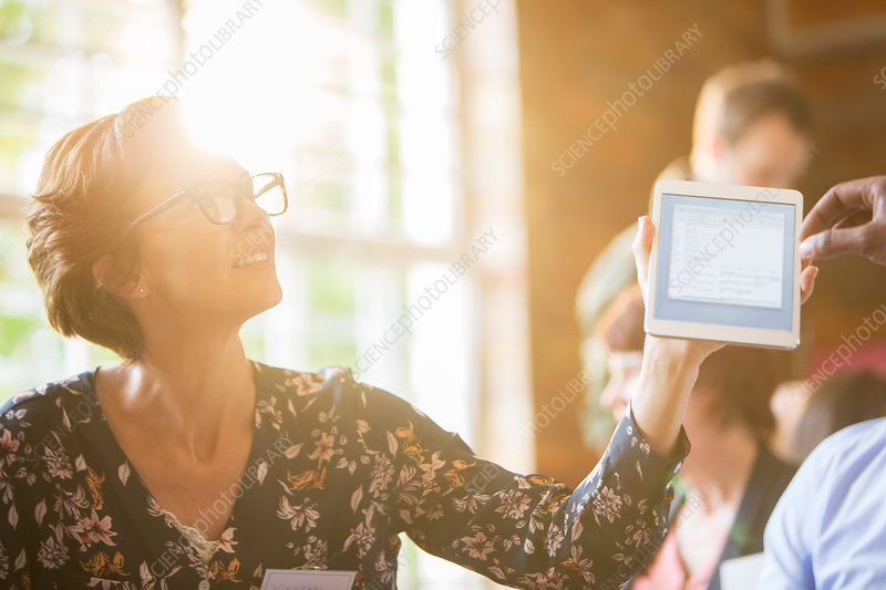 Woman using tablet in sunny meeting