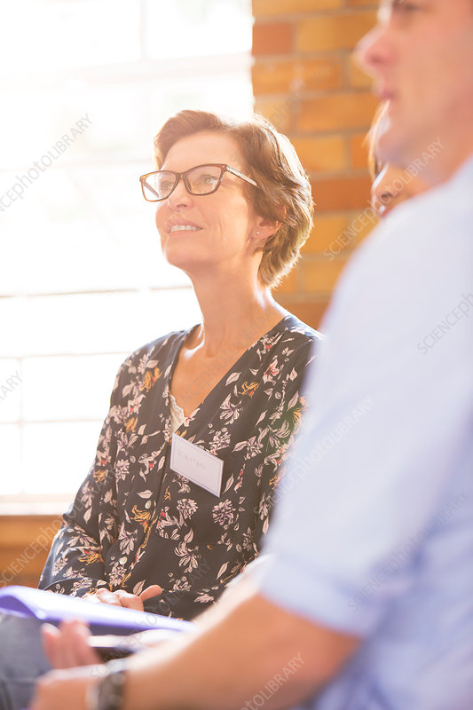 Smiling woman listening in meeting