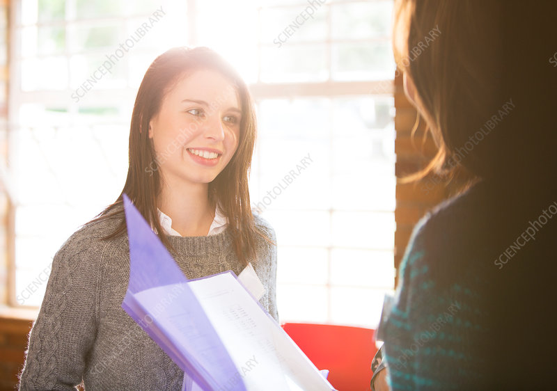 Smiling businesswomen with paperwork
