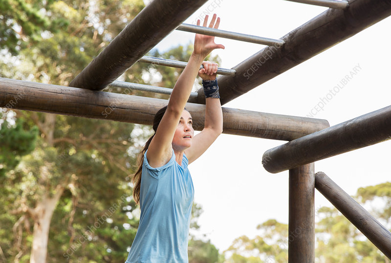 Determined woman crossing monkey bars