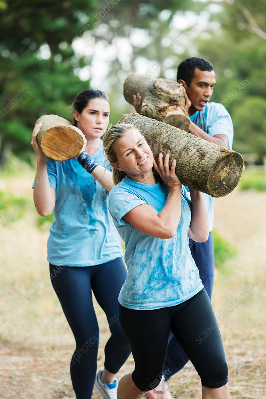 Determined woman running with log