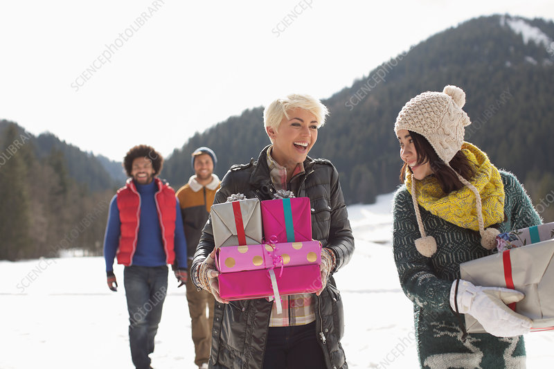 Friends carrying Christmas gifts in snow