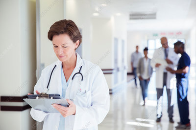 Doctor using tablet in hospital corridor