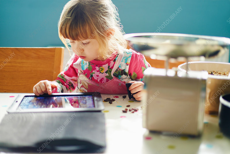 Curious girl using digital tablet