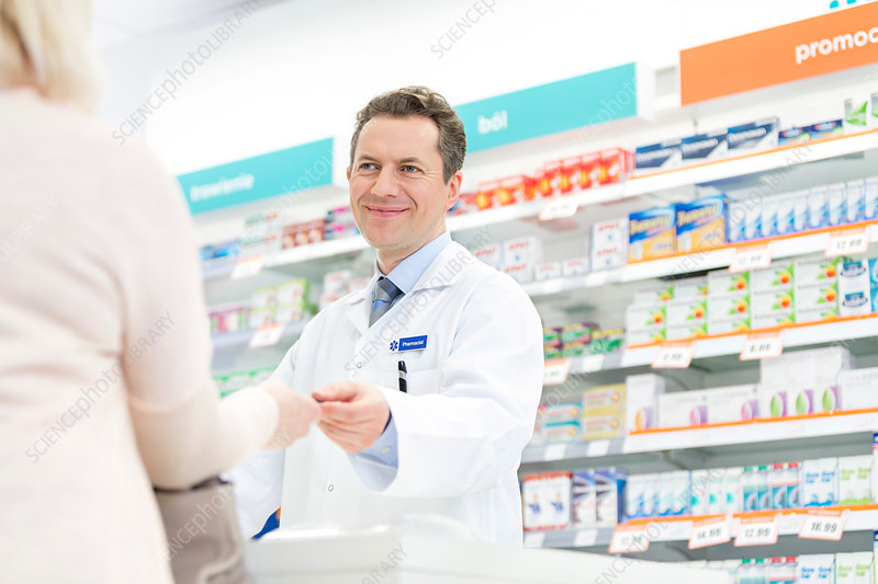 Smiling pharmacist assisting customer