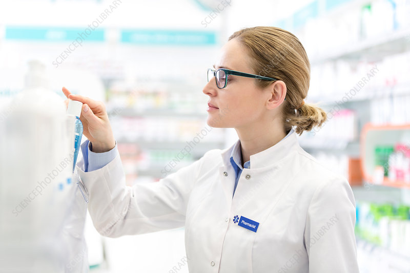 Pharmacist removing bottle from shelf