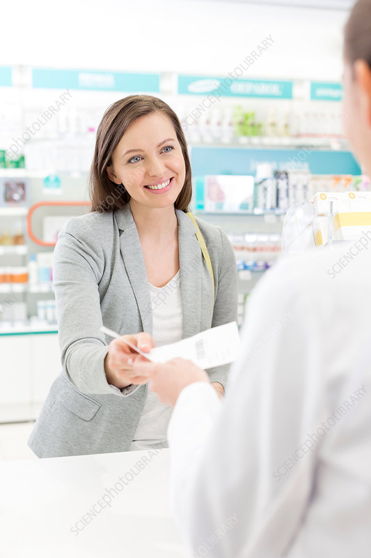 Smiling customer giving prescription
