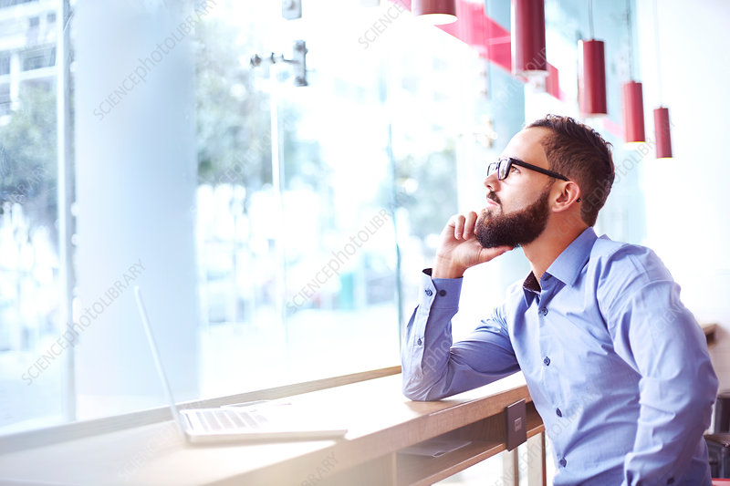 Pensive businessman at laptop in cafe