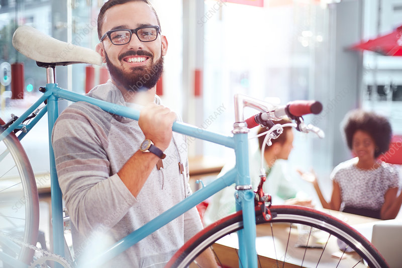 Smiling man carrying bicycle in cafe