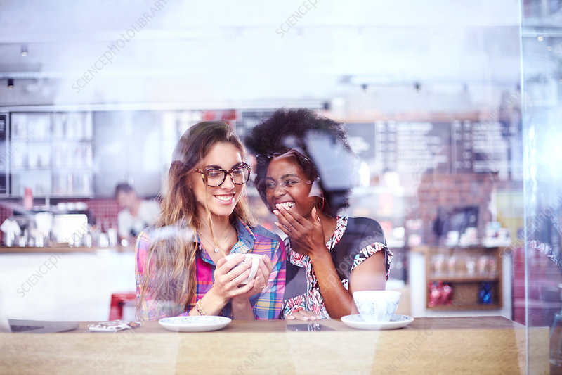 Women laughing and drinking coffee window