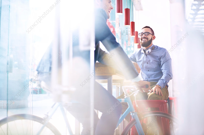 Smiling man on bicycle in cafe
