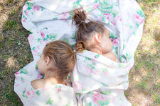 Twin girls napping in floral sheet