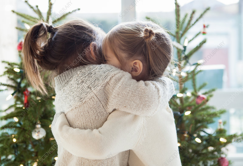 Girls hugging in front of Christmas trees