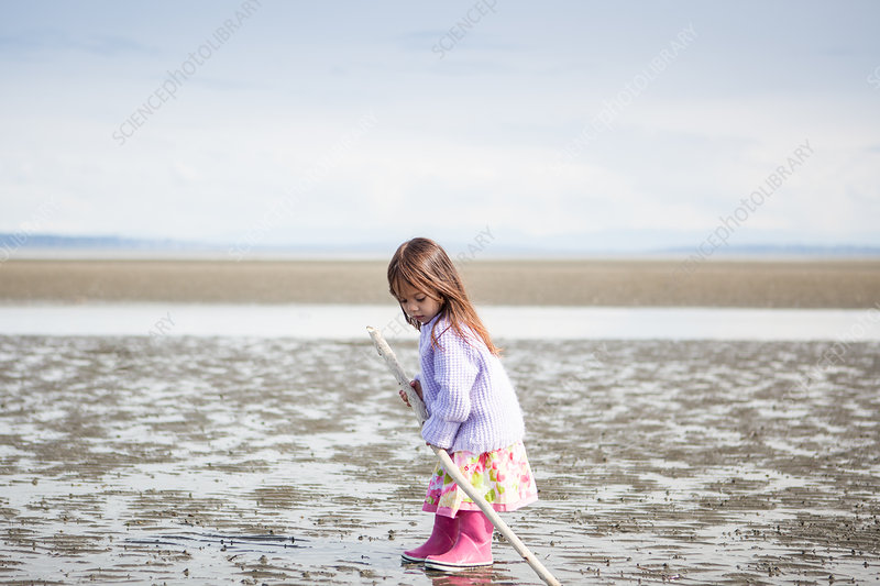 Girl with stick playing on beach