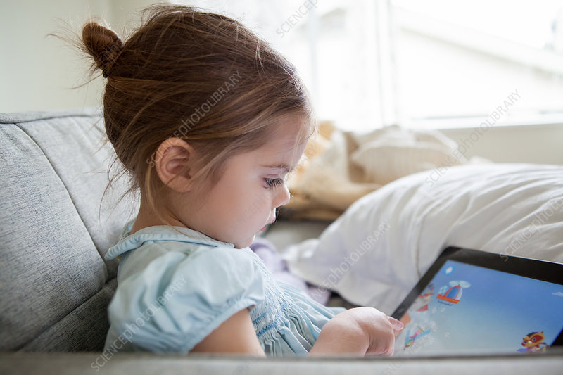 Girl using digital tablet on sofa