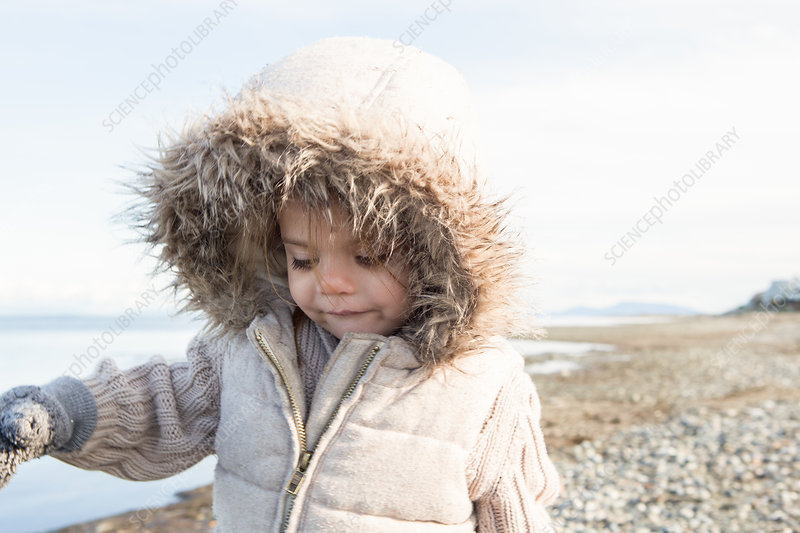 Girl in fur hood jacket walking on beach