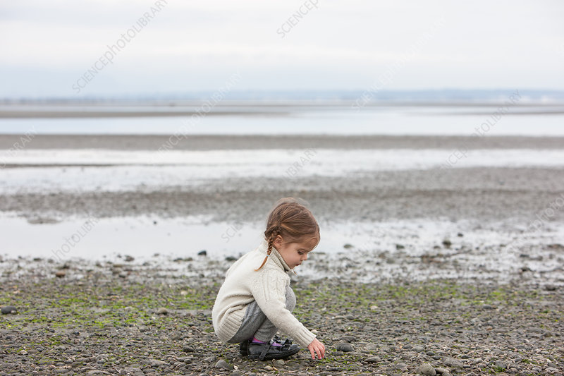 Girl picking up pebbles on beach