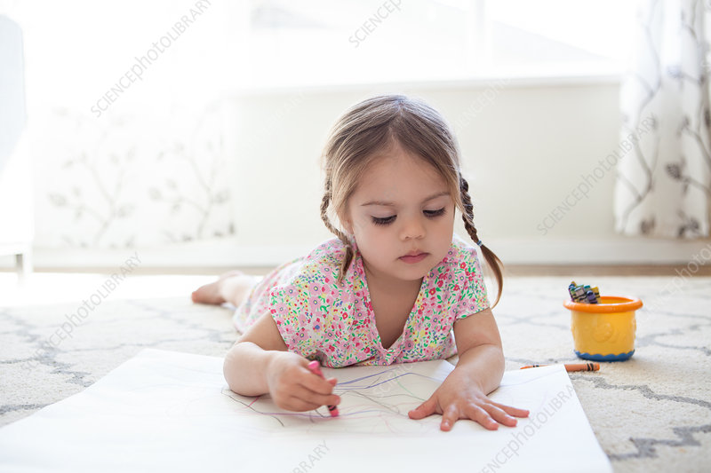 Girl on floor drawing with crayons