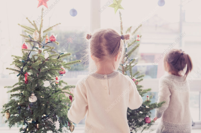 Girls decorating small Christmas trees