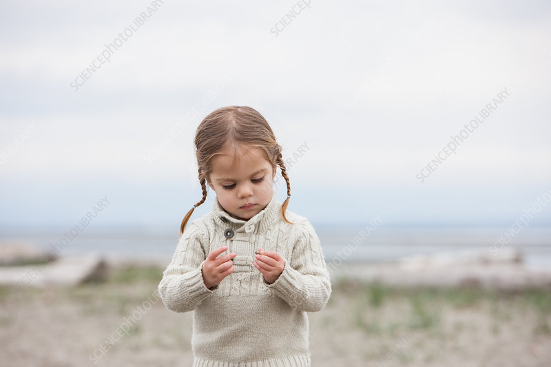 Curious girl examining pebbles on beach