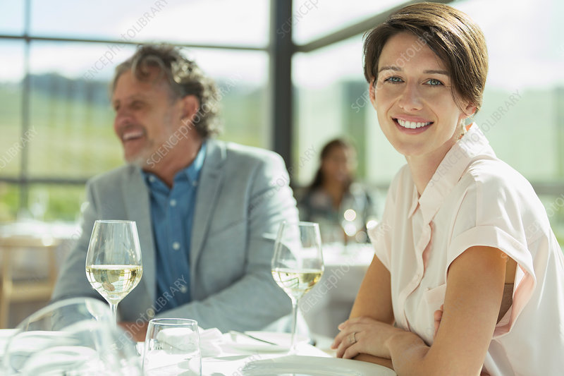 Woman drinking wine in sunny restaurant