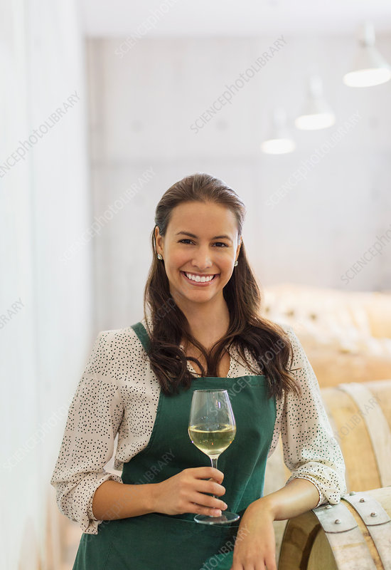 Vintner with white wine in cellar