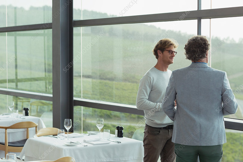 Men talking at winery dining room window