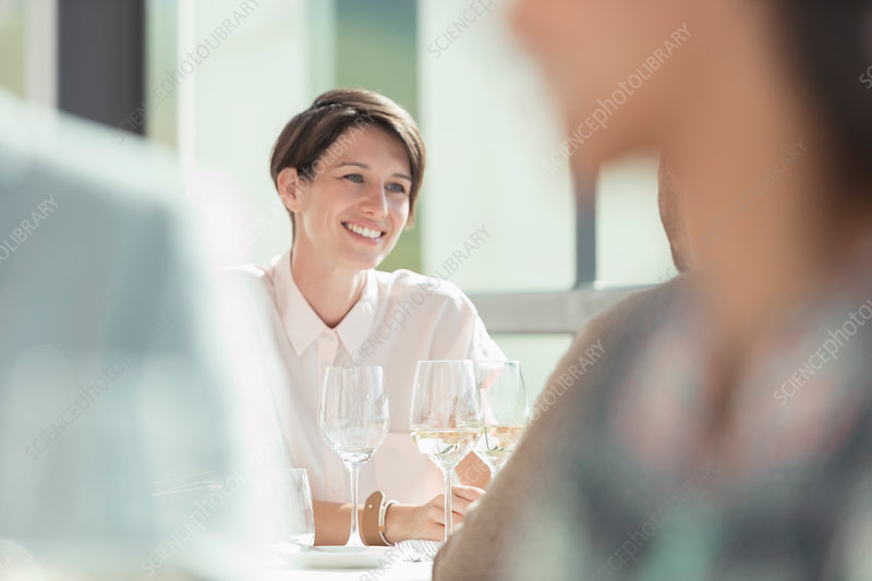 Smiling woman drinking white wine