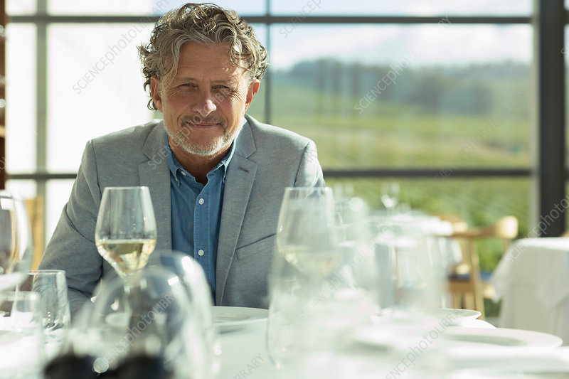 Portrait confident man with white wine at sunny restaurant t