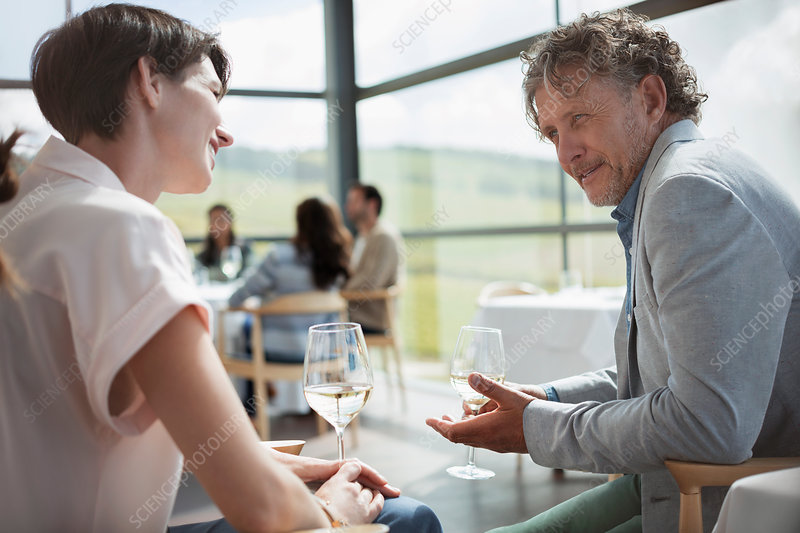 Couple drinking wine and talking in restaurant