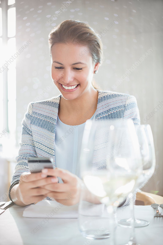 Smiling woman texting at restaurant table