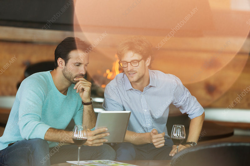 Men drinking red wine and using tablet