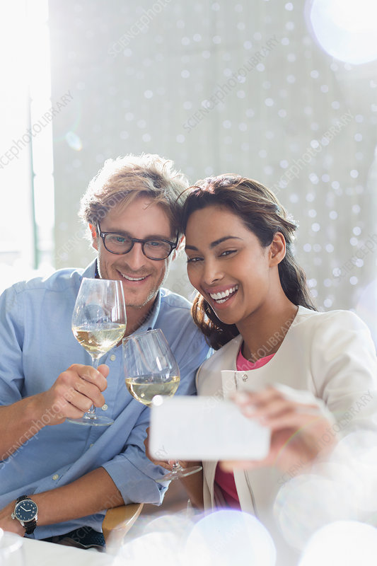 Couple with white wine taking selfie