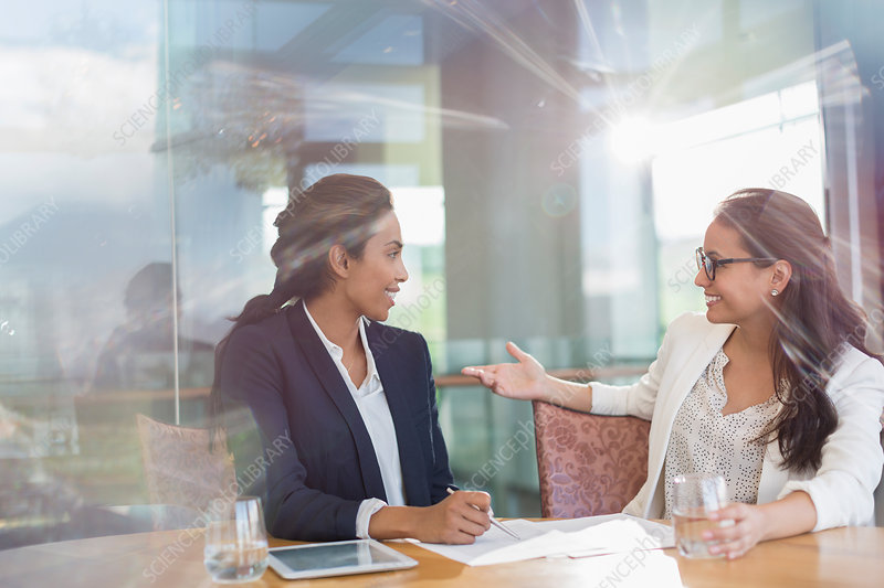 Businesswomen talking in sunny conference room