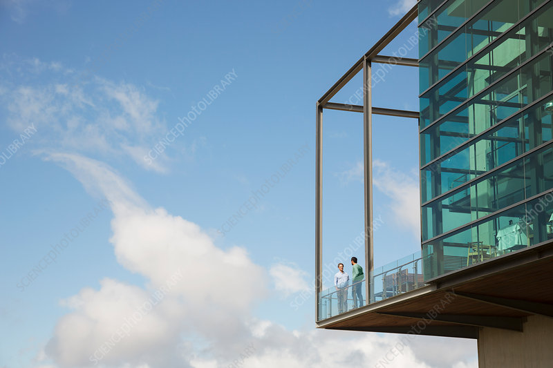 Men talking on balcony of glass bump out against blue sky