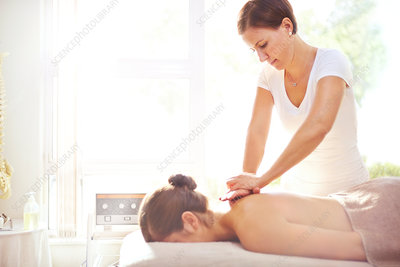 Woman receiving massage by masseuse