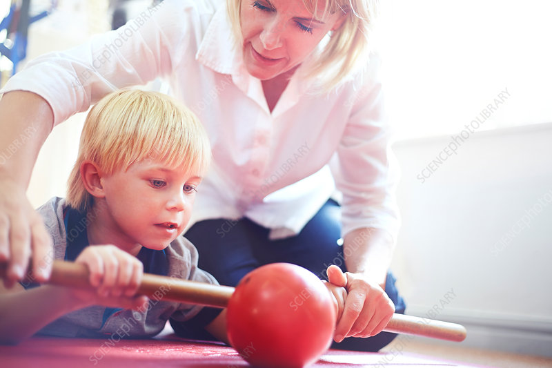 Physical therapist guiding boy