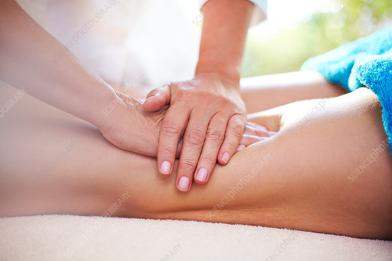 Masseuse rubbing woman's legs