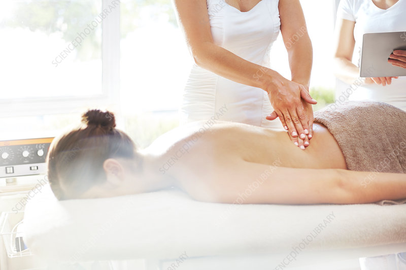 Masseuse massaging woman's back