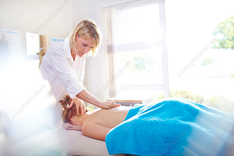 Physical therapist massaging woman's back