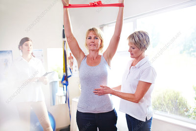 Physical therapist guiding woman