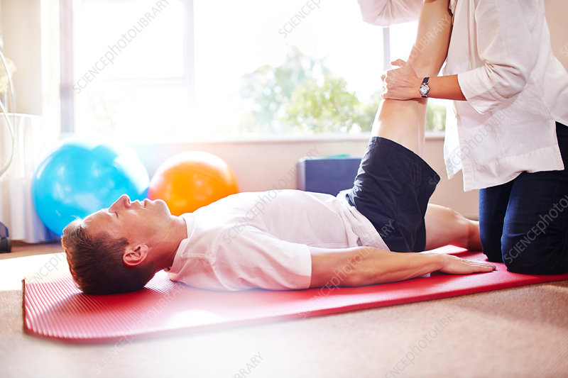 Physical therapist stretching man's leg